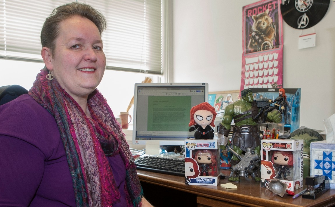 UC English professor Rebecca Borah poses with her office collection of Marvel memorabilia.