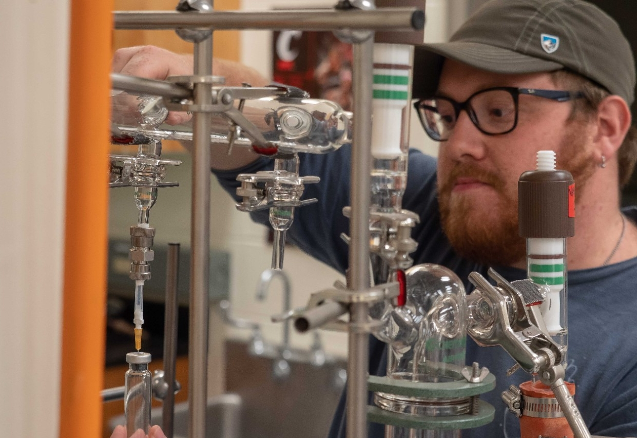 UC graduate student Jacob Deighton uses a vacuum line to prepare a sample in a geology lab.