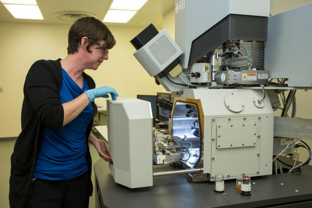 Melodie Fickenscher, director of the materials lab, removes a sample from a dual-beam scanning electron microscope.