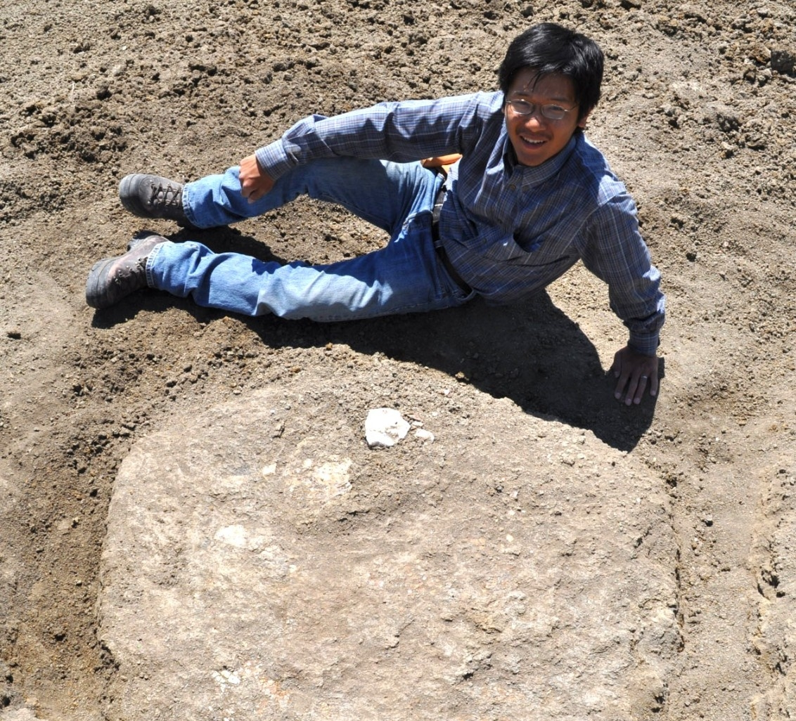 UC paleontologist Takuya Konishi poses with an ammonite fossil he discovered in Alberta, Canada, in 2011. (Photo by Darren Tanke/Royal Tyrrell Museum of Paleontology)