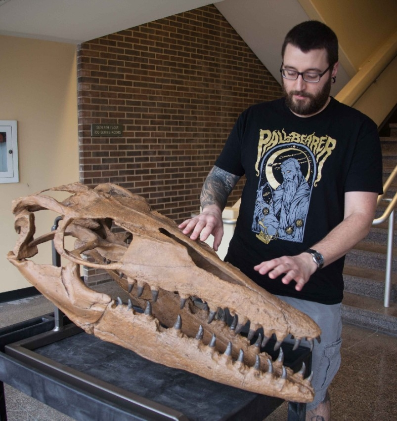 UC graduate student Samuel Garvey examines a cast of a mosasaur skull.