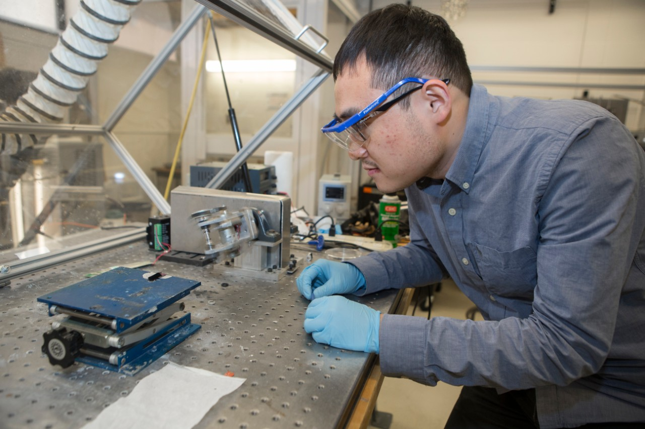 UC research assistant Yanbo Fang pulls carbon nanotube fiber into a machine that spools it into thread.
