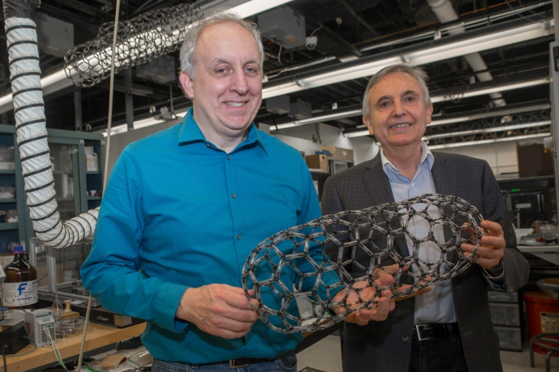 UC professors Mark Schulz, left, and Vesselin Shanov co-direct UC's Nanoworld Laboratories. Here they hold up a model of a carbon nanotube capsule.