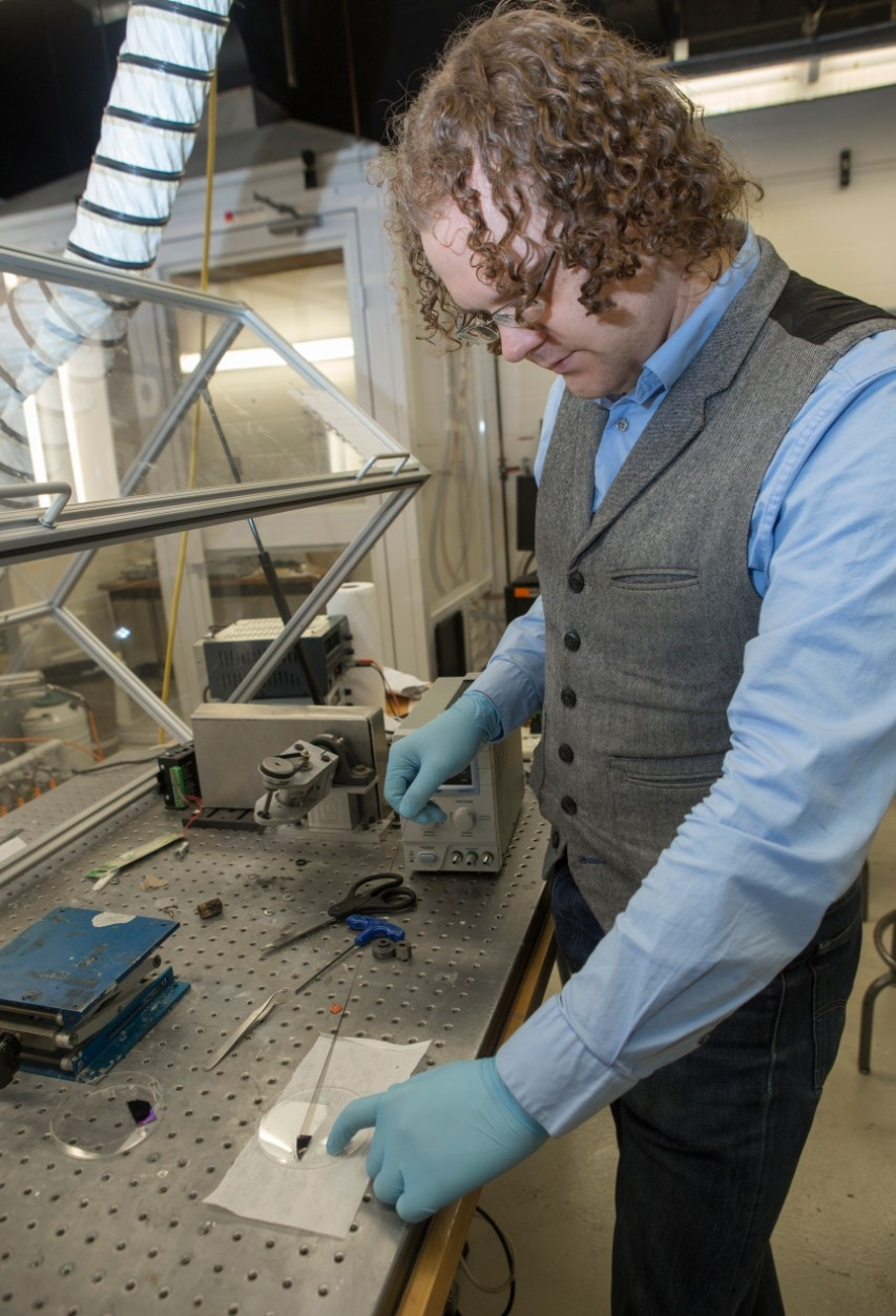 UC graduate student Mark Haase stretches carbon nanotube fiber grown in UC's Nanoworld Lab. Like spider silk, it's stretchy and strong.