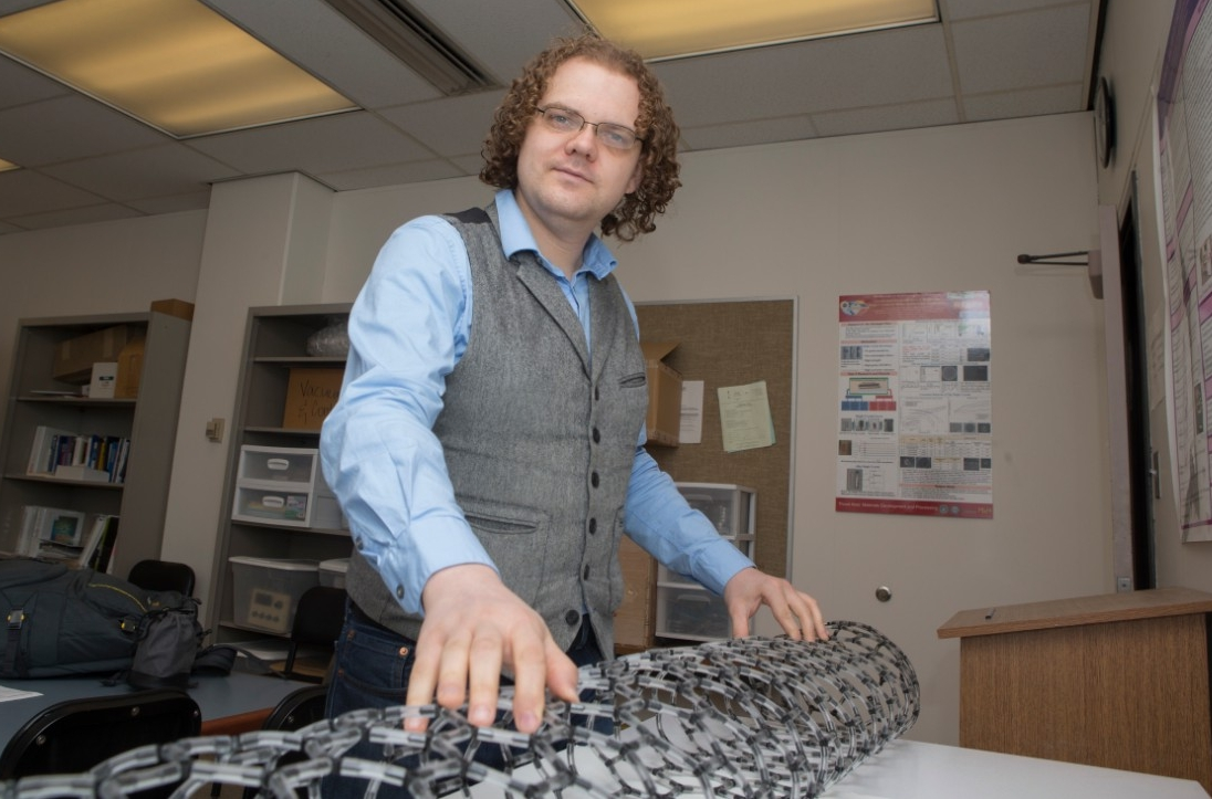 UC graduate student Mark Haase is conducting experiments using carbon nanotubes at UC's Nanoworld Laboratories and at Wright Patterson's Air Force Research Lab. A model in front of him demonstrates their lattice structure.
