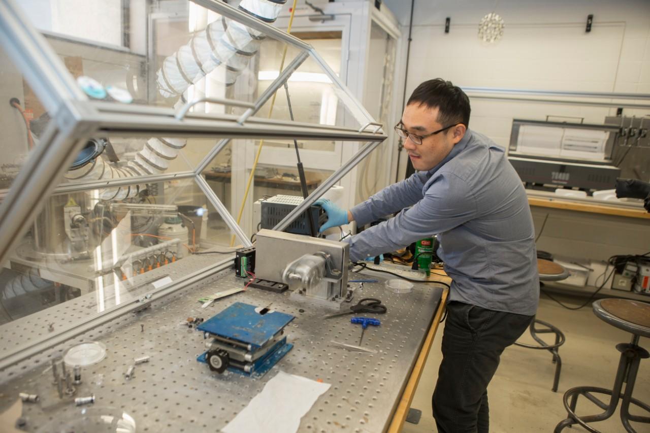 UC engineering student Yanbo Fang spools carbon nanotube fiber into a fine thread using a custom spinning machine in UC's Nanoworld Laboratories.