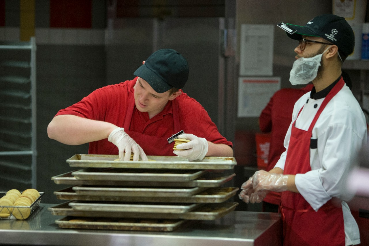 A student worker places cookies on a baking sheet while his co-worker, a natural support, looks on.