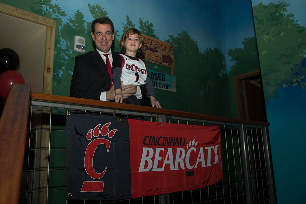 UC Director of Athletics Mike Bohn with a young fan.