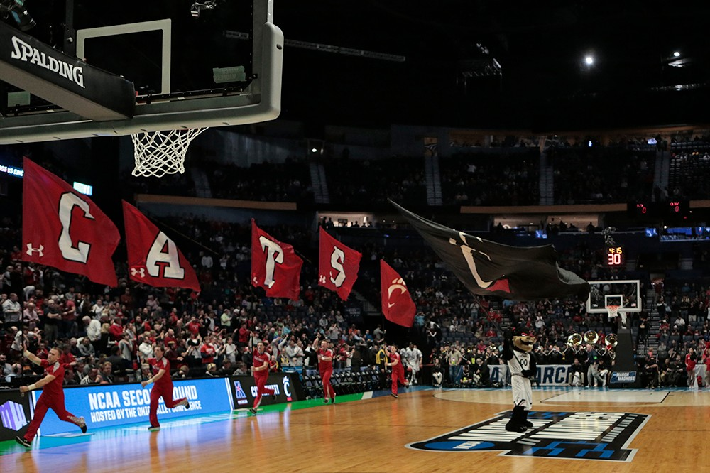 UC cheerleaders run with flags onto the court.