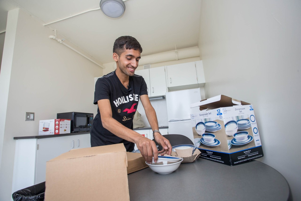 Sudarshan Pandey puts away dishes in his new home at Scioto Hall.