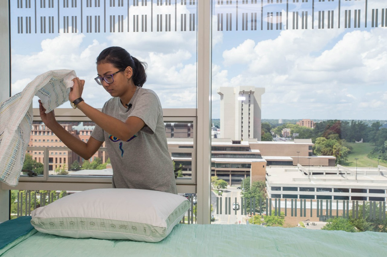 Pranita Dhungana makes her bed in her new home at Scioto Hall. Photo/Andrew Higley/UC Creative Services