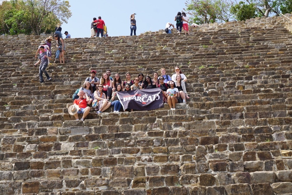 UC study abroad students sit on steps of a pyramid in Monte Alban near Oaxaca, Mexico.