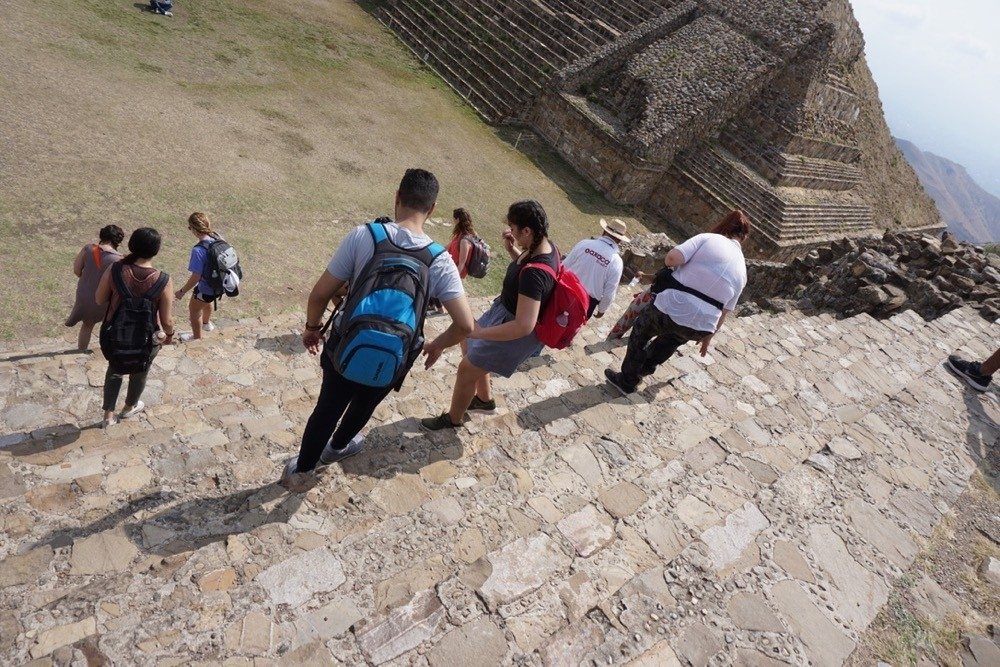 UC study abroad students climb steps of a pyramid in Monte Alban near Oaxaca, Mexico.