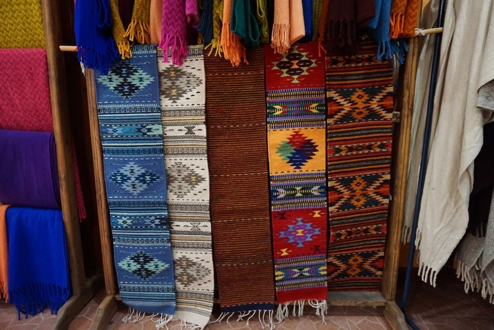 Colorful hand loomed rugs hang on wall in Oaxaca, Mexico.