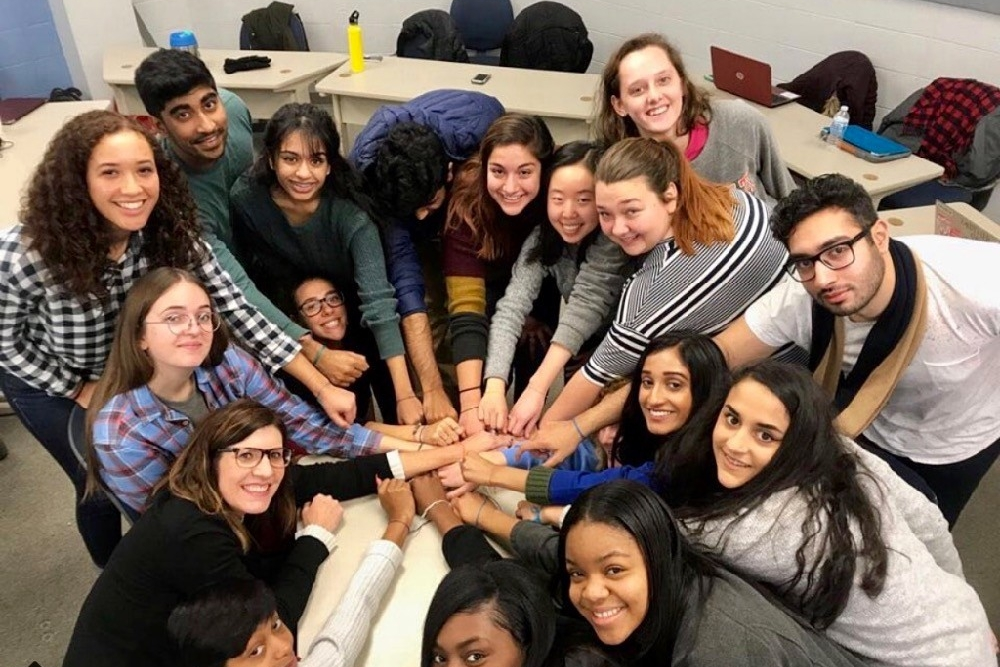 UC's Robin Selzer stands together with her study abroad class clasping hands in a circle before going to Oaxaca, Mexico.