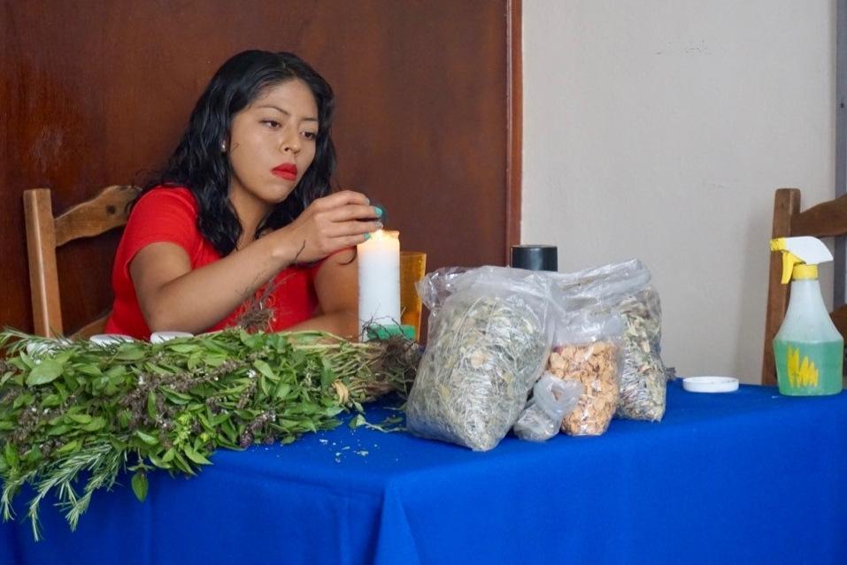 A local curandero folk healer sits at table of herbs used in healing ceremony in Oaxaca, Mexico.