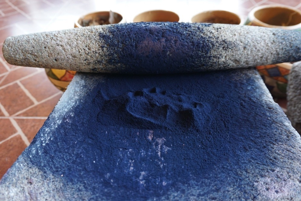 Large stone bowl and roller mashing blue rock to make dye in Oaxaca, Mexico.