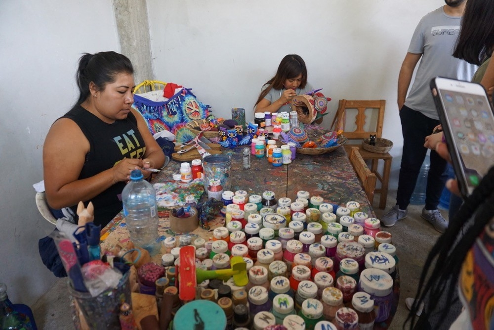 Local woman sits at table of hand made dyes and jars of colors in Oaxaca, Mexico.