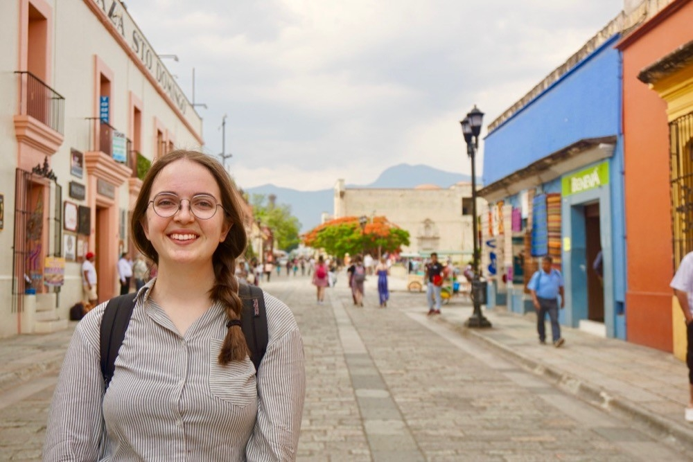 UC study abroad student stands among the colorful street art in Oaxaca, Mexico.