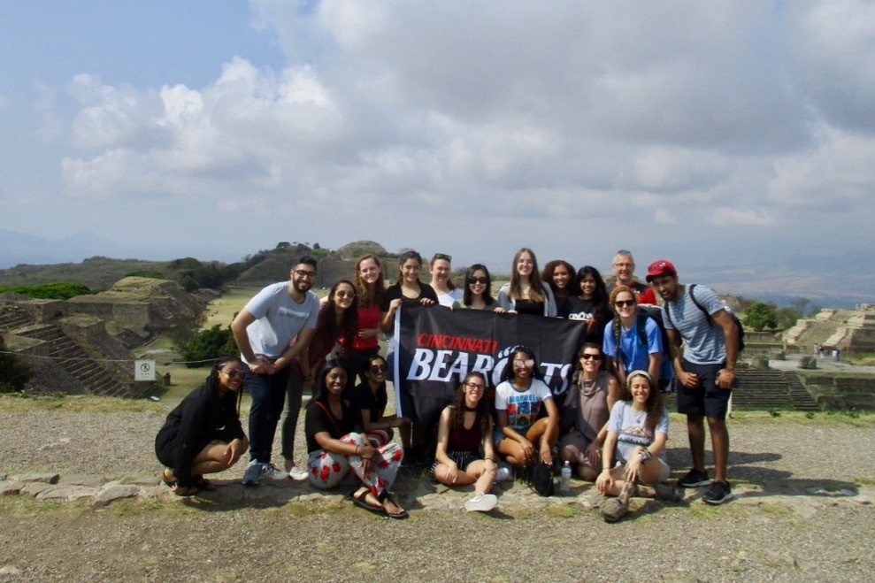 UC study abroad students stand together behind a UC flag in Monte Alban, an ancient archaeological site near Oaxaca. Mexico.