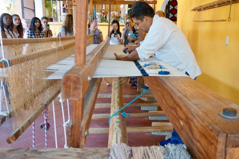 A man works on a hand powered loom making a rug in Oaxaca, Mexico.