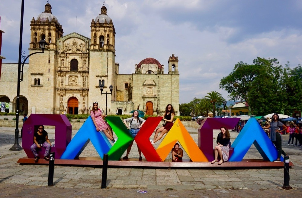 UC study abroad students stand among the giant colorful letters that spell out the city's name in the center of Oaxaca City, Mexico.