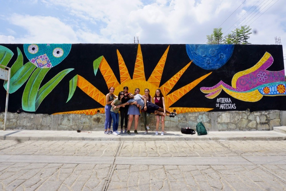 UC study abroad students stand in front of one of the many colorful political street art murals in Oaxaca, Mexico.