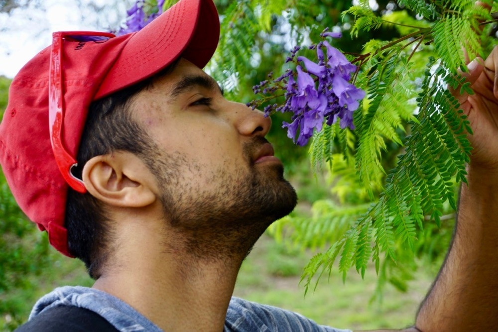 UC student Rohan Srivastava smells a purple flower while on study abroad in Oaxaca, Mexico in 2018.