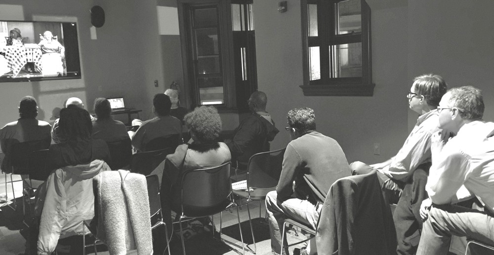 People sitting at a film screening held at the Clifton Public Library.