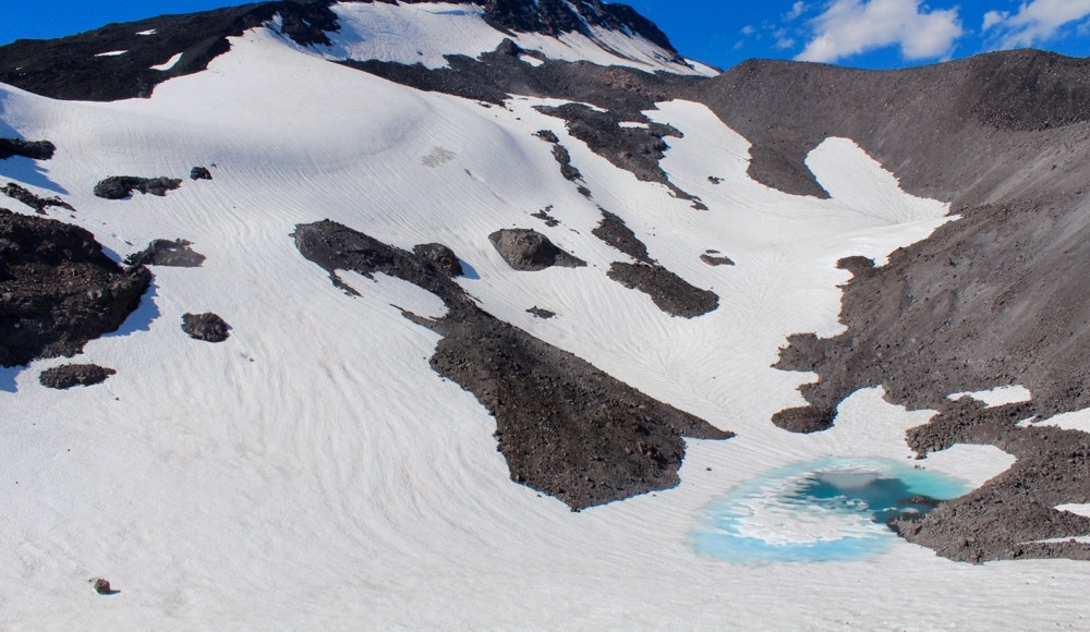 Gotchen Glacier covered in snow with a meltwater blue pool in lower left.