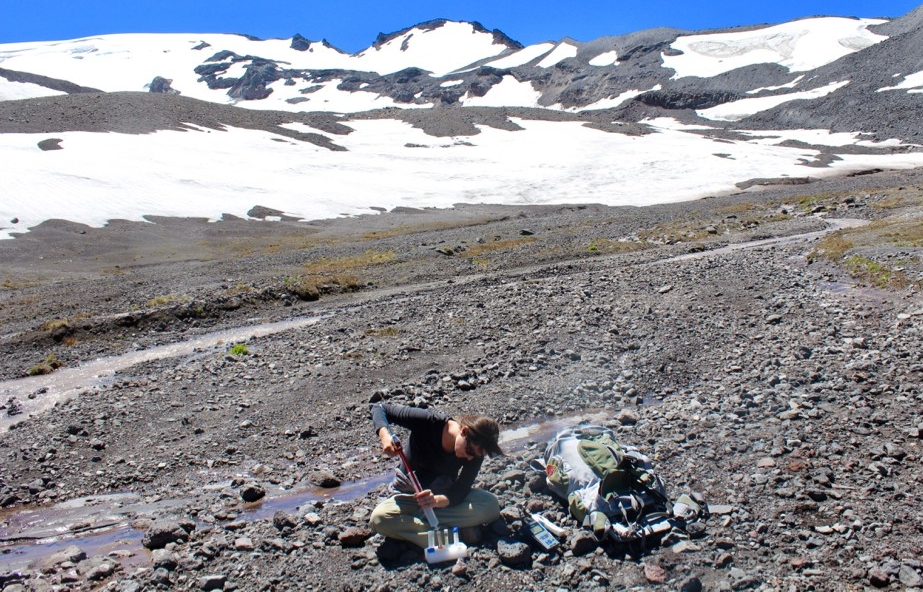 Professor Trinity Hamilton filtering a water sample at the base of Collier Glacier on North Sister, Oregon.