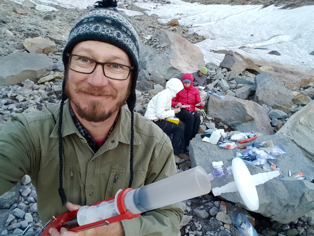 UC Professor Jeff Havig holds a large syringe during pink snow sample analysis on Eliot Glacier, Mt. Hood, Oregon.