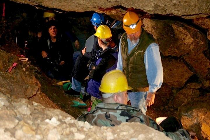 People wearing hard hats inside a dark, narrow cave tunnel.