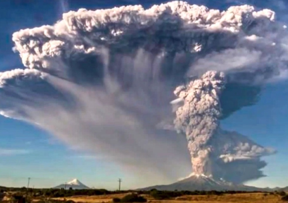 Volcanic ash cloud shoots high into the sky from an active volcano.
