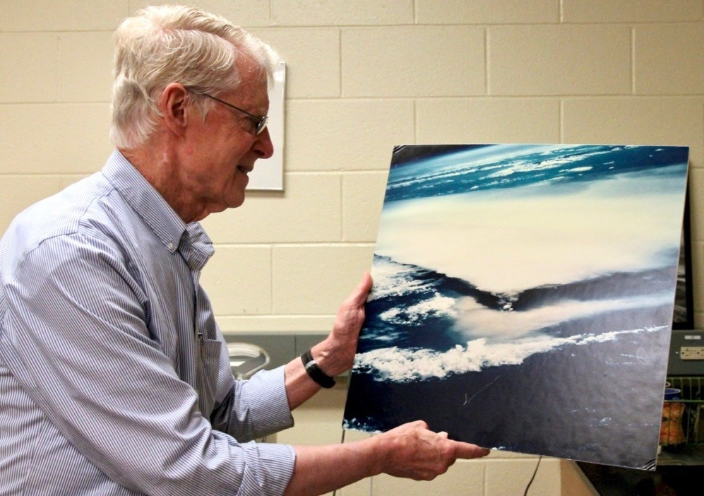 UC professor of geology, Warren Huff, holds up a photo of a volcano.