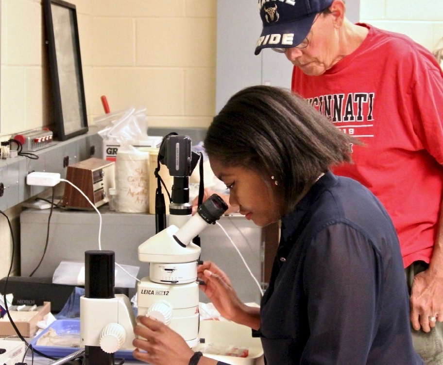 UC anthropologist Kenneth Tankersley and grad student Dominique Sparks-Stokes look at minerals through a microscope.