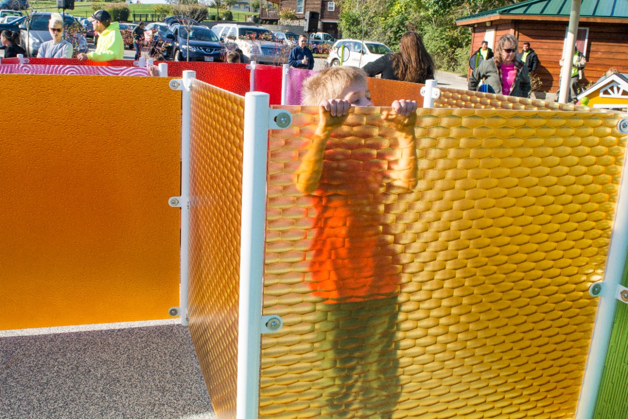 A child peeks over the top of a colored panel in the maze.