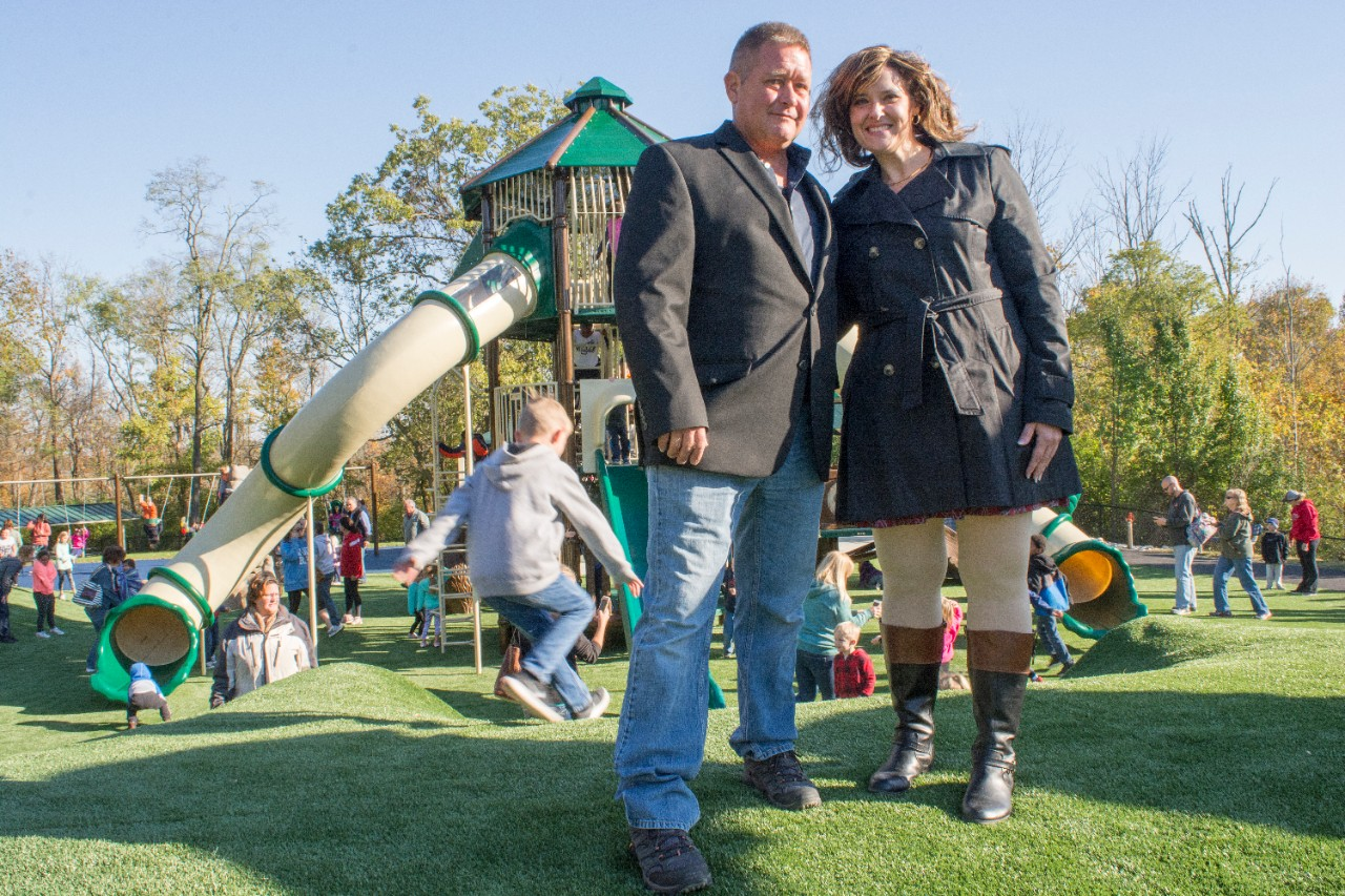 Eric Schmidt and Tina Stanton-Chapman stand atop a hill in the new playground.