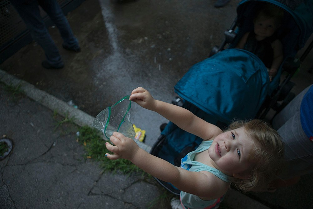 A child catches raindrops in a plastic bag.