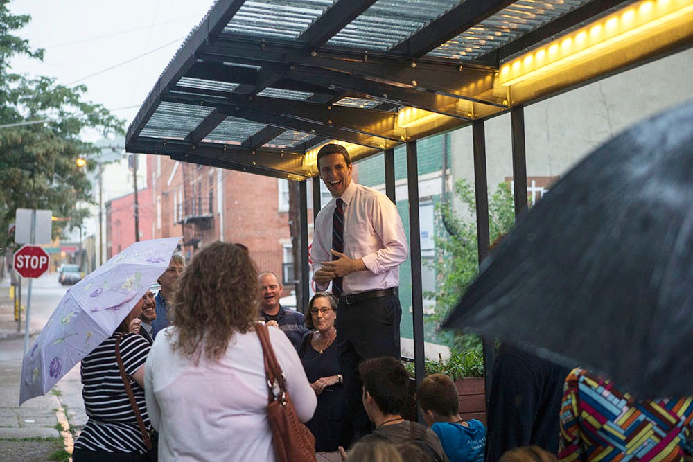 City councilman P.G. Sittenfeld addresses the crowd from inside the parklet as rain pours down.
