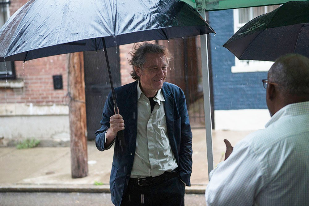 DAAP Dean Robert Probst stays dry under an umbrella.