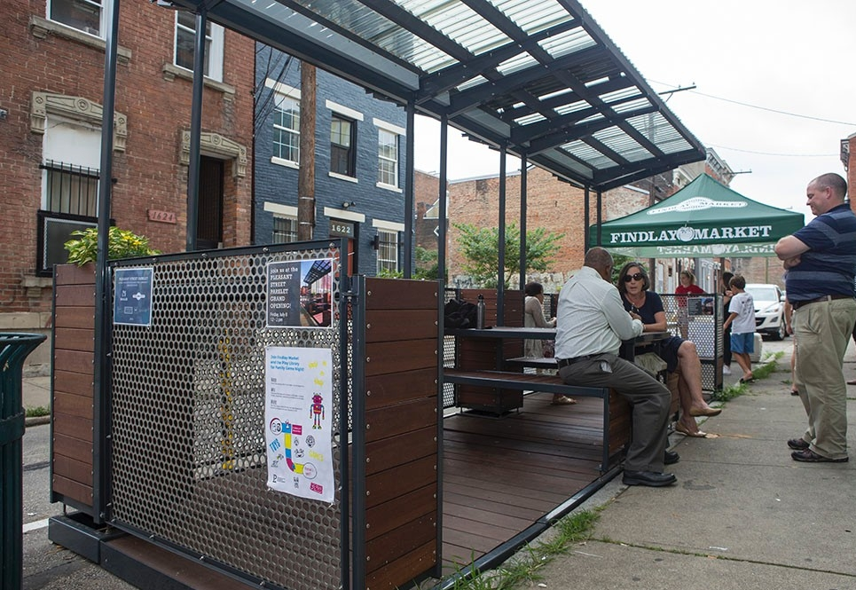 Two people chat in the parklet, which features wood seating and tabletops.