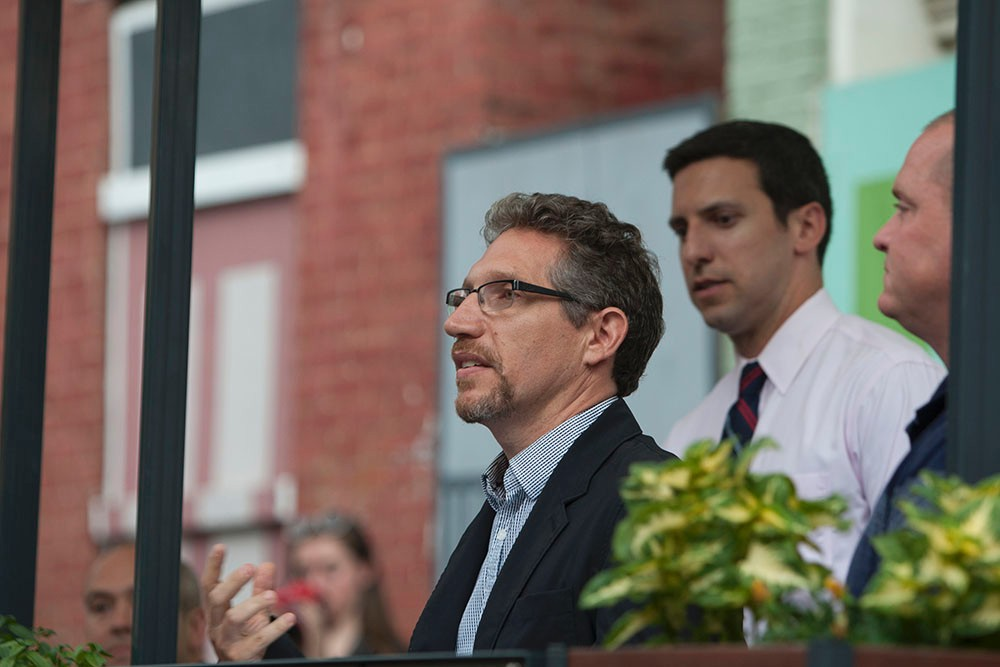 Michael Zaretsky speaks to a crowd at the grand opening of the Pleasant Street parklet.