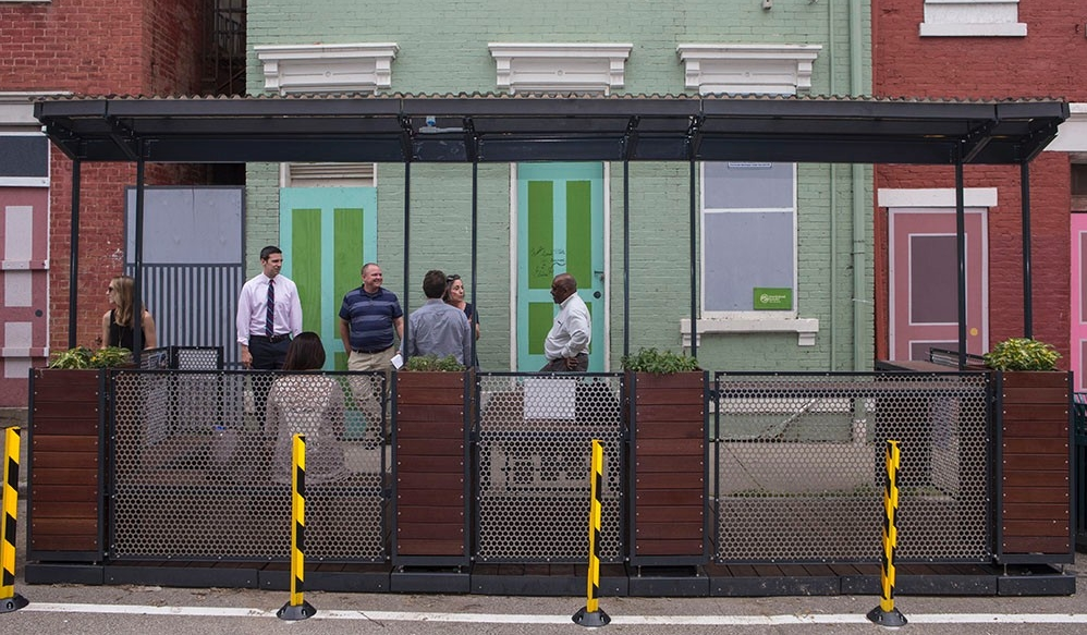 Community members gather inside and around MetroLAB's parklet — a tiny public park located in a street parking spot.