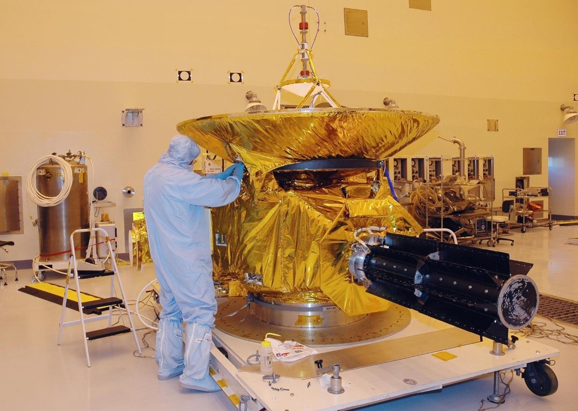 A technician wraps the half-ton New Horizons spacecraft in a protective heat shield at the Kennedy Space Center. (NASA)