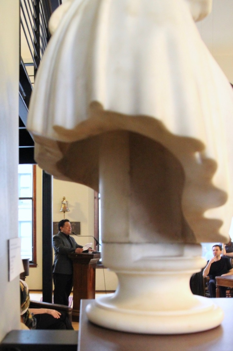 Manuel Iris stand at a podium behind a 19th-century marble bust in Cincinnati's Mercantile Library