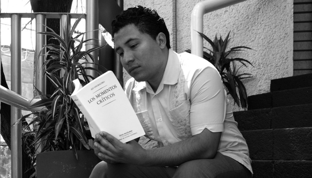 UC alum Manuel Iris, Cincinnati's second Poet Laureate, reads from a poetry book.
