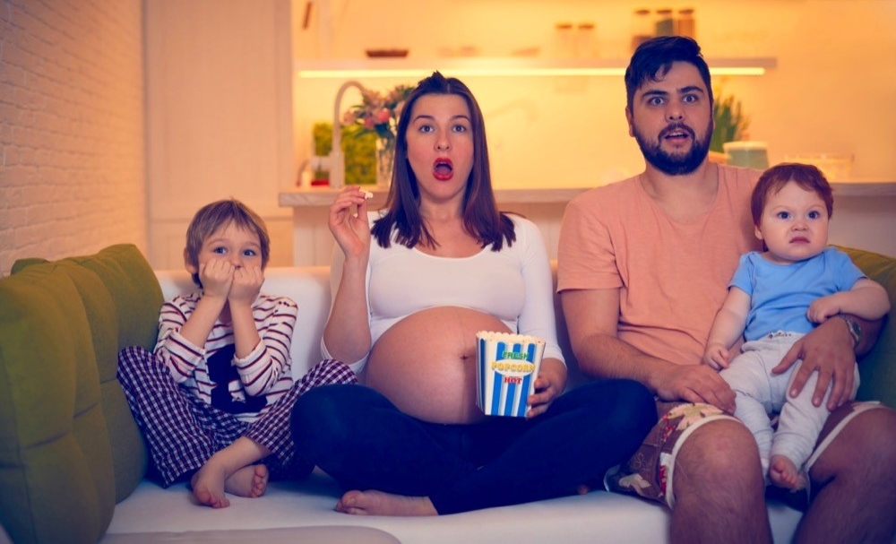 A family (including pregnant mom) sit on a couch looking shocked as they watch TV. photo/Adobestock