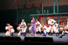 Leslie Kritzer, CCM '99, dances on the stage with the ball team.