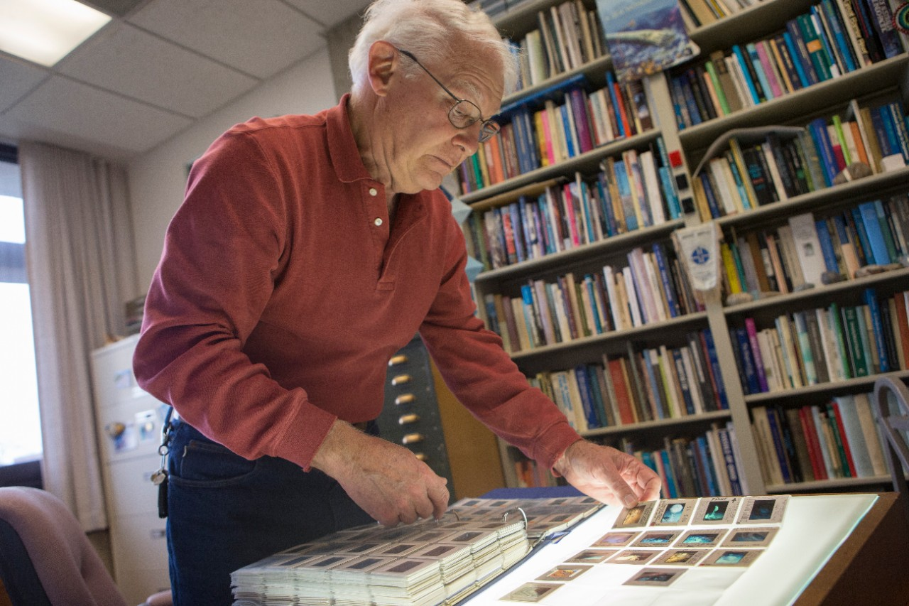 UC professor emeritus David Meyer leafs through his collection of underwater photography he preserved in slides at his office in the Geology-Physics Building.